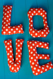 The letters with red polka dot fabric. LOVE on blue wooden background Stock Photography