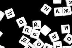 The letters of the Russian alphabet for a child`s game scattered on a dark background. Close up stock photo
