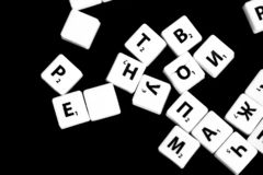 The letters of the Russian alphabet for a child`s game scattered on a dark background. Close up stock photography