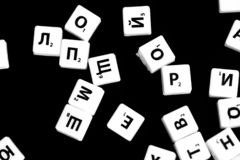 The letters of the Russian alphabet for a child`s game scattered on a dark background. Close up stock images