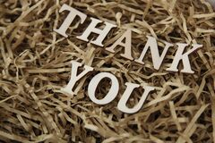 Letters sitting on brown shredded paper forming the words Thank you