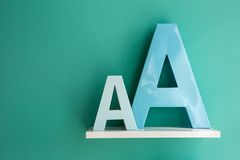 Letters A small and big size turquoise color on a. White shelf. Shelf installed on a wall in a horizontal position. Fragment of interior decor stock image