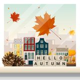 Letters spelling hello autumn on wooden table top with autumn cityscape background Stock Images