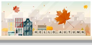 Letters spelling hello autumn on wooden table top with autumn cityscape background Stock Image