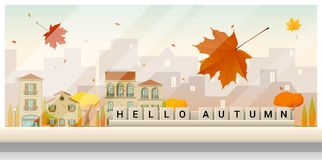 Letters spelling hello autumn on wooden table top with autumn cityscape background Stock Photo