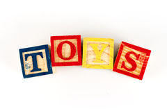 The letters T,O,Y,S spelling toys with wooden blocks.  Stock Images