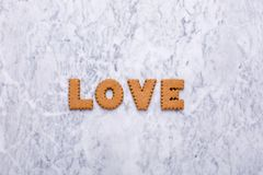 Letters tasty cookies Love on marble background royalty free stock photos