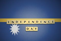 Letters with text independence day on the national flag of Nauru. Royalty Free Stock Images