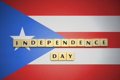 Letters with text independence day on the national flag of puerto rico. Royalty Free Stock Photos