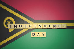 Letters with text independence day on the national flag of Vanuatu. Royalty Free Stock Image