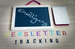 Letters with the words Newsletter Tracking to clarify tracking technologies with newsletters and the word in german Einwilligung i. N english consent royalty free stock photography
