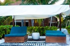 Letti di sofà blu sulla spiaggia per rilassamento e yoga Fotografia Stock Libera da Diritti