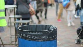 Lettiera di lancio della gente in secchio della spazzatura, inquinamento ambientale, consumismo globale video d archivio