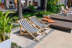 Lettini di legno con il materasso dal lato della piscina immagine stock libera da diritti