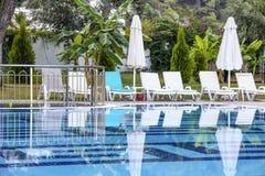 Lettini ed ombrelli dalla piscina Immagine Stock Libera da Diritti