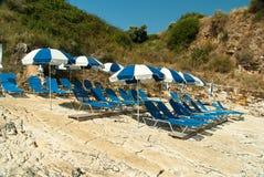 Lettini ed ombrelli (parasoli) sulla spiaggia nell'isola di Corfù, Grecia Fotografia Stock