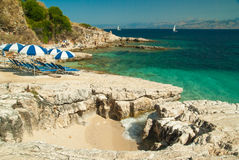 Lettini ed ombrelli (parasoli) sulla spiaggia nell'isola di Corfù, Grecia Immagine Stock