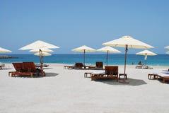 Lettini ed ombrelli sulla spiaggia dell'oceano Immagini Stock