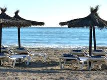Lettini ed ombrelli sulla spiaggia vuota in Spagna fotografia stock