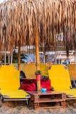 Lettini gialli sulla spiaggia con gli ombrelli - Nea Vrasna, Grecia immagini stock libere da diritti