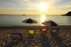 Lettino ed ombrello alla riva sul fondo di tramonto Fotografia Stock