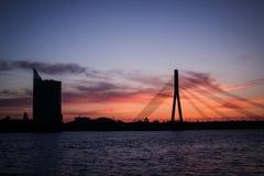 Lettische Flagge bei Sonnenuntergang lizenzfreie stockbilder