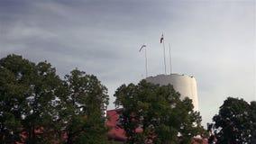 Lettische Flagge und lettischer Präsidentenstandard von Riga ziehen sich Turm zurück stock video