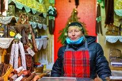Lettische Frau, die traditionelle Waren am Riga-Weihnachtsmarkt verkauft Lizenzfreie Stockfotografie