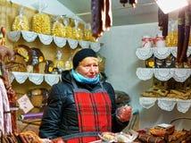 Lettische Frau, die traditionelle Waren am Riga-Weihnachtsmarkt verkauft Stockfotografie