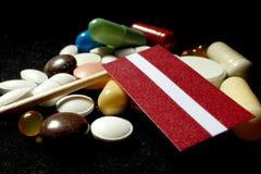 Lettisk flagga med lotten av medicinska preventivpillerar som isoleras på svart bakgrund Royaltyfria Bilder