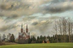Lettiskt byfält med traktoren Royaltyfri Bild