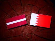 Lettland flagga med den bahrainska flaggan på en isolerad trädstubbe Royaltyfri Fotografi