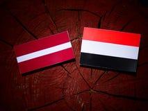 Lettland flagga med den jemenitiska flaggan på en trädstubbe Arkivbild