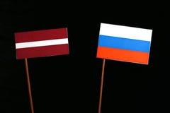 Lettland flagga med den ryska flaggan på svart Arkivbilder