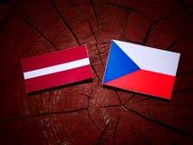 Lettland flagga med den tjeckiska flaggan på en trädstubbe Royaltyfria Bilder