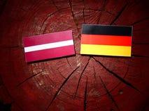 Lettland flagga med den tyska flaggan på en trädstubbe Arkivbilder