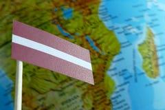 Lettland flagga med en jordklotöversikt som en bakgrund Arkivfoton