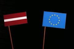 Lettland flagga med EU-flaggan för europeisk union på svart Fotografering för Bildbyråer