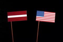 Lettland flagga med USA flaggan på svart Arkivfoton