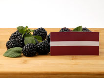 Lettland flagga på en träpanel med björnbär som isoleras på en wh Arkivfoton