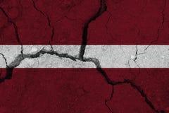 Lettland-Flagge auf der gebrochenen Erde lizenzfreie stockfotos