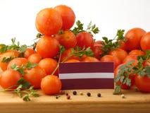 Lettland-Flagge auf einer Holzverkleidung mit den Tomaten lokalisiert auf einem Weiß Stockfotos