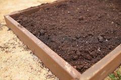 Letto alzato vuoto appena preparato del giardino in primavera immagini stock libere da diritti