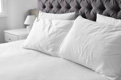 Letto comodo con tela ed i cuscini bianchi fotografia stock libera da diritti