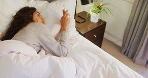 Letto di menzogne della donna facendo uso del suo telefono cellulare nella camera da letto 4K 4k stock footage
