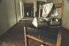 Letto di ospedale in una stanza abbandonata in rovine con la luce che viene attraverso le finestre Fotografie Stock