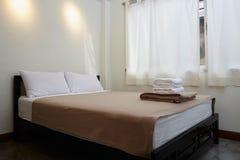 Letto a due piazze bianco, due cuscini ed asciugamano Immagine Stock