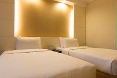 Letto gemellato nella camera da letto dell'hotel fotografia stock
