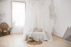 Letto matrimoniale con biancheria da letto ed il baldacchino grigi bedroom Una sedia di vimini fatta di legno nell'angolo della s fotografie stock