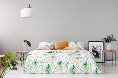 Letto matrimoniale con il piumino floreale ed il cuscino colorato pesca fra due comodini di legno con i fiori in vasi su  immagini stock